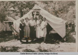 "Young women stand in front of a tent ""Larchmont Heights, M.E.""at the Institute Camp,..."