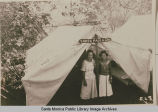 "Young women stand in front of a tent ""Santa Paula"" at the Institute Camp, Temescal..."
