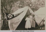 "Young women stand in front of  a tent ""Whittier""at the Institute Camp, Temescal Canyon,..."